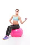 Молодая спортсменка работая при гантели сидя на fitball Стоковая Фотография