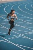 Молодая спортсменка sprinting на идущем стадионе следа Стоковые Изображения RF