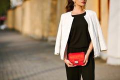 Молодая стильная женщина идет в город с красной ультрамодной сумкой На плече сумки девушки, одетом в черных брюках стоковые фотографии rf
