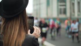 Молодая стильная женщина стоя на дороге и фотографируя группа людей бежать марафон для дальнего расстояния сток-видео