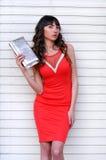 Молодая стильная сексуальная женщина в красном элегантном платье лета стоя в передней белой предпосылке, смотря камеру Стоковые Фотографии RF