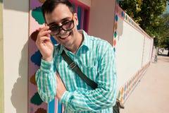 Молодая стильная уверенно счастливая смеясь над красивая модель человека в голубой t-коротком с солнечными очками 3 все изменение Стоковые Изображения RF