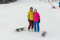 Молодая стойка snowboarders пар на зимний день Стоковые Фото