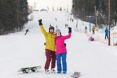 Молодая стойка snowboarders пар на зимний день Стоковое Изображение RF