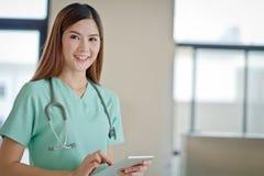 Молодая сторона улыбки женщины доктора при стетоскоп смотря таблетку co Стоковое Изображение