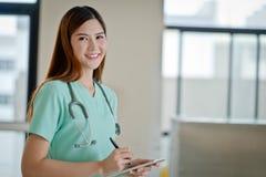 Молодая сторона улыбки женщины доктора при стетоскоп смотря таблетку co Стоковые Изображения