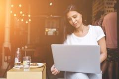 Молодая студентка используя портативный компьютер для учить пока сидящ в кафе Стоковые Изображения RF