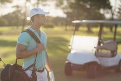 Молодая сумка нося игрока гольфа Стоковые Изображения