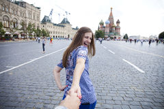 Молодая счастливая девушка вытягивает руку парней на красной площади в Москве Стоковые Изображения