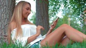 Молодая счастливая девушка делая selfie сидя на траве в парке сток-видео
