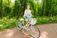 Молодая счастливая девушка при ее велосипед стоя на кирпичах в парке Стоковая Фотография