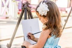 Молодая счастливая девушка ребенка рисуя изображение outdoors стоковая фотография rf