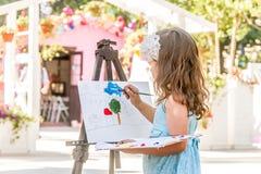 Молодая счастливая девушка ребенка рисуя изображение outdoors стоковые фото