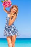 Молодая счастливая девушка с букетом цветка на тропических море и пляже b стоковое фото