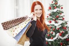 Молодая счастливая девушка с сумками рождества стоковые изображения rf