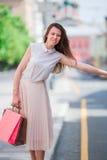 Молодая счастливая девушка с хозяйственными сумками улавливает такси Портрет красивой счастливой женщины стоя на удерживании улиц Стоковые Изображения RF