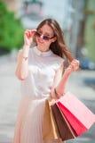 Молодая счастливая девушка с хозяйственными сумками outdoors Портрет красивой счастливой женщины стоя на удерживании улицы Стоковые Изображения