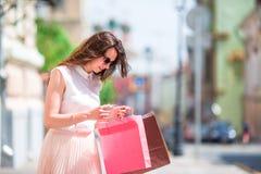 Молодая счастливая девушка с хозяйственными сумками outdoors Портрет красивой счастливой женщины стоя на удерживании улицы Стоковое Изображение