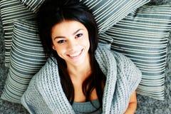 Молодая счастливая женщина лежа на поле с подушками. Взгляд сверху Стоковые Фотографии RF