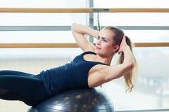 Молодая счастливая женщина делая фитнес работает с шариком пригонки дома Стоковая Фотография RF