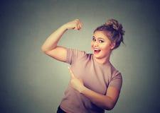 Молодая счастливая женщина изгибая мышцы показывая ей прочность красивейшая потеря принципиальной схемы живота над женщиной веса  Стоковые Фотографии RF