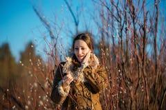 Молодая счастливая женщина одела пальто и шарф овчины Девушка держа ветви вербы Время весны… подняло листья, естественная предпос Стоковые Изображения