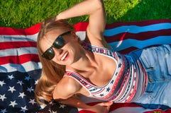 Молодая счастливая женщина патриота на флаге Соединенных Штатов стоковое изображение rf
