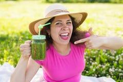 Молодая счастливая женщина показывает на зеленых smoothies на пикнике Здоровые еда, вытрезвитель и концепция диеты Стоковые Фото