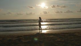 Молодая счастливая женщина при шарф стоя на пляже океана на заходе солнца наслаждаться летом девушки Женский силуэт в бикини видеоматериал