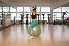 Молодая счастливая женщина работая с шариком фитнеса стоковая фотография rf
