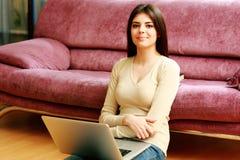 Молодая счастливая женщина сидя на поле и используя компьтер-книжку Стоковое Фото