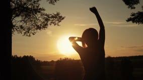 Молодая счастливая женщина скача, танцуя и имея потеха в лесе на заходе солнца сток-видео
