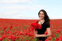 Молодая счастливая женщина с букетом красных маков Стоковые Изображения