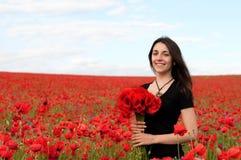 Молодая счастливая женщина с букетом красных маков Стоковые Фотографии RF