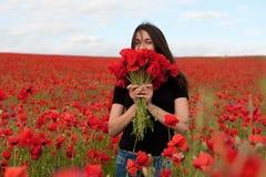 Молодая счастливая женщина с букетом красных маков Стоковое Изображение RF