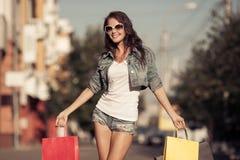 Молодая счастливая женщина с хозяйственными сумками идя на улицу стоковое изображение rf