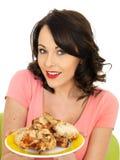Молодая счастливая здоровая женщина держа плиту сваренных холодом Drumsticks цыпленка Стоковое Изображение RF
