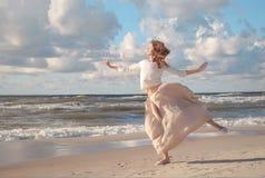 Молодая счастливая красивая женщина скача на пляж в лете Изображение женщины скача над океаном на заходе солнца, силуэтом Стоковые Изображения