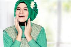 Молодая счастливая красивая мусульманская женщина с зеленый носить костюма высокий стоковые изображения