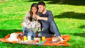Молодая счастливая пара наслаждаясь пикником в парке пока он держит бокал вина и ей принимает selfie Стоковые Фото
