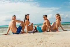 Молодая счастливая потеха havin друзей на пляже Стоковые Фотографии RF