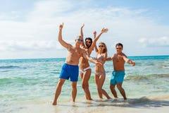 Молодая счастливая потеха havin друзей на пляже Стоковые Изображения