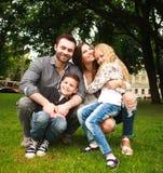 Молодая счастливая семья с 2 детьми в парке зеленого цвета лета Стоковые Фото