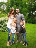 Молодая счастливая семья с 2 детьми в парке зеленого цвета лета Стоковое Фото