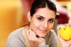 Молодая счастливая усмехаясь женщина держа желтое яблоко Стоковая Фотография RF