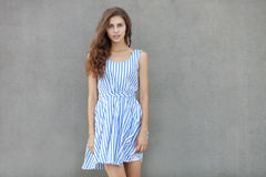 Молодая счастливая усмехаясь красивая женщина в светлом платье при длинное вьющиеся волосы брюнет представляя против стены на теп Стоковое Изображение RF