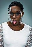 Молодая счастливая чернокожая женщина вставляя вне ее язык Стоковое Изображение
