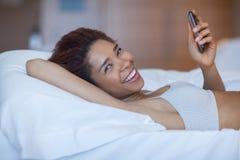 Молодая счастливая чернокожая женщина лежа в кровати Стоковые Изображения