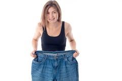 Молодая тощая девушка держащ огромные брюки изолированные на белой предпосылке стоковое изображение rf