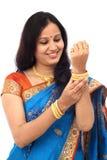 Молодая традиционная индийская женщина смотря bangles золота Стоковые Изображения RF